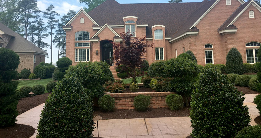 Landscaping and shrubs with brick house